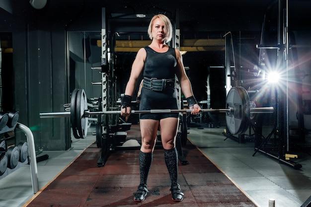 Donna giovane muscolare di forma fisica che solleva un crossfit di peso in palestra.