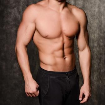 Giovane uomo sexy muscoloso in un berretto con un torso nudo su sfondo nero