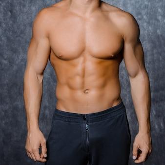 Giovane uomo sexy muscoloso in un berretto con un torso nudo su sfondo nero Foto Premium