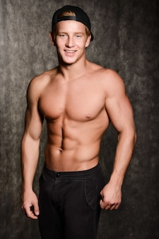Giovane uomo sexy muscoloso in un berretto con un torso nudo sul nero