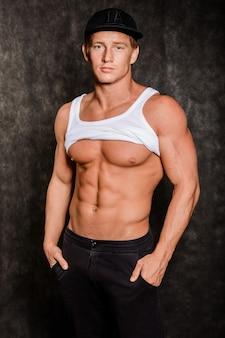 Giovane uomo sexy muscoloso in una maglia e un berretto con un torso nudo sul nero