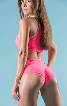 Atleta muscolare della giovane donna che posa allo studio su fondo blu