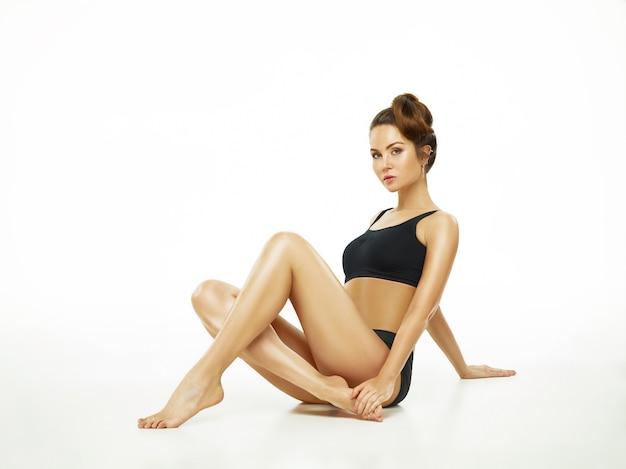 Atleta muscolare della giovane donna che posa allo studio