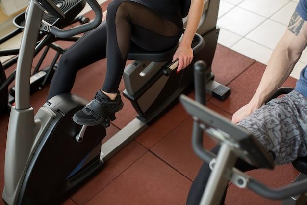 Giovane donna muscolare che risolve sulla cyclette in palestra, intenso allenamento cardio.