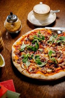 Pizza ai funghi con aggiunta di mozzarella ed erbe aromatiche su un tavolo di legno, vista dall'alto