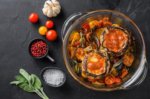 Funghi, cotti al forno e farciti con ingredienti formaggio cheddar, pomodorini e salvia in vaso di vetro su sfondo di pietra nera topview spazio per il testo.