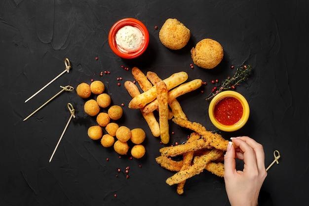 Funghi in pastella palline di formaggio bastoncini di formaggio e anelli di formaggio in pastella su fondo nero con h...