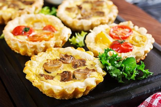 Tortini di funghi, cheddar, pomodori sul tavolo di legno. mini torte. delizioso antipasto, tapas, merenda.