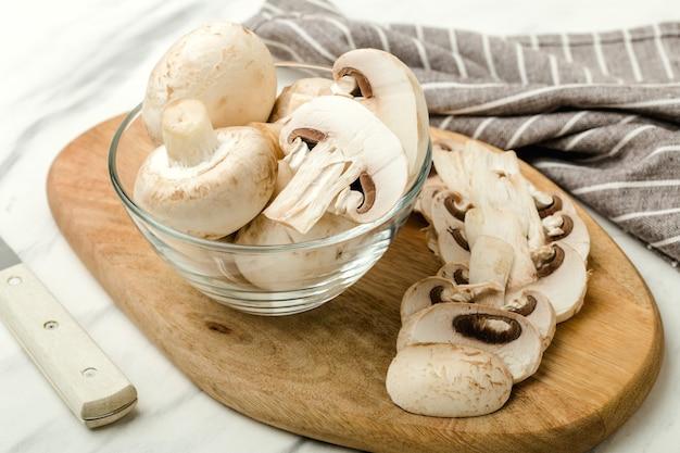 Funghi in una ciotola di vetro trasparente, su una tavola di legno, funghi a fette, asciugamano a strisce marrone, sfondo chiaro,