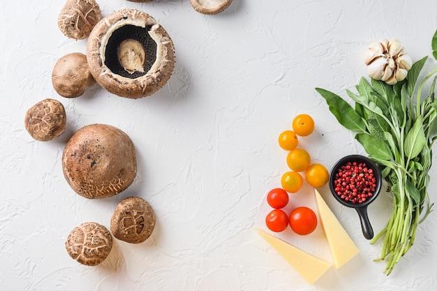 Funghi ingredienti per cuocere portobello, formaggio cheddar, pomodorini e salvia su sfondo bianco vista dall'alto concetto spazio incorniciato per il testo.