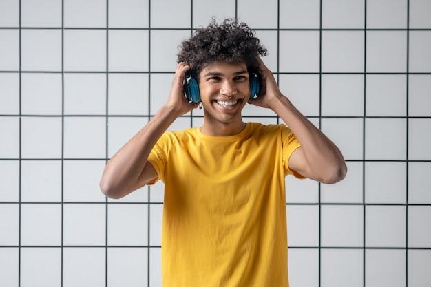 Musica. ragazzo giovane afroamericano in auricolari sorridendo e guardando contento
