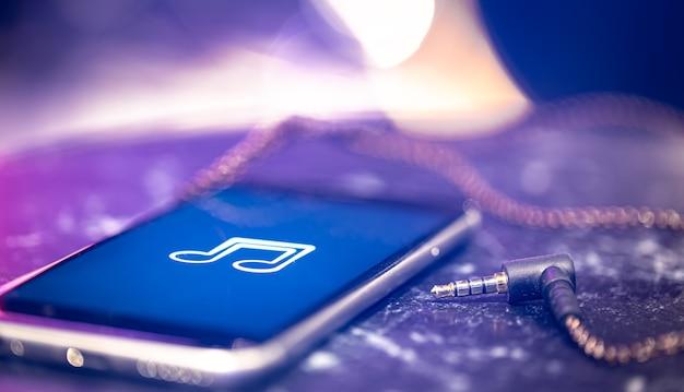 Musica di sottofondo con un'icona di ascolto della musica sul telefono e sulle cuffie.