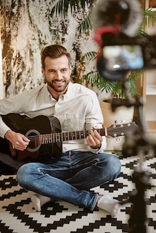 Blogger musicale che suona la chitarra e sorride, mentre registra una lezione online per i suoi iscritti.