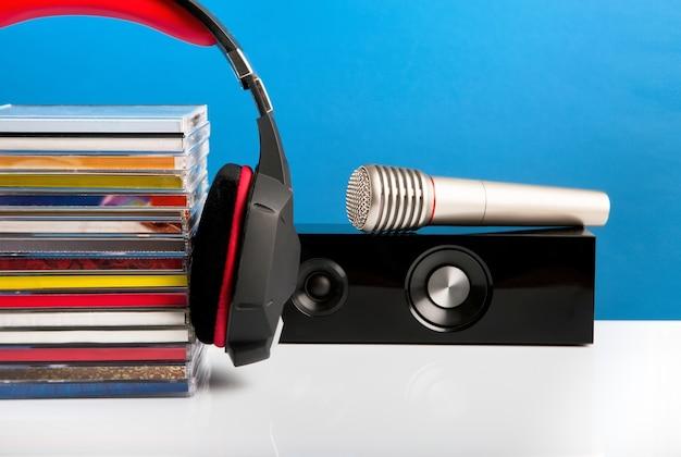 Cuffie della colonna di musica con cd e un microfono audio su un tavolo di legno su un verde