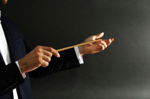 Mani del direttore d'orchestra con la bacchetta sul nero