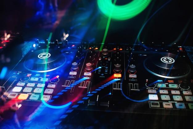 Console musicale e mixer per dj in discoteca con effetti colorati