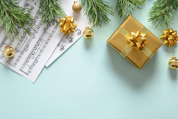 Cornice musicale per canti e canti natalizi decorati con palline d'oro su blu