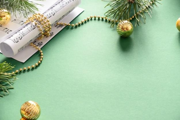 Cornice musicale per canti e canti natalizi decorati con palline d'oro su verde