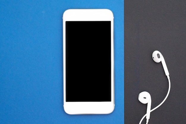 Musica, gadget, amante della musica. smartphone bianco su nero e blu