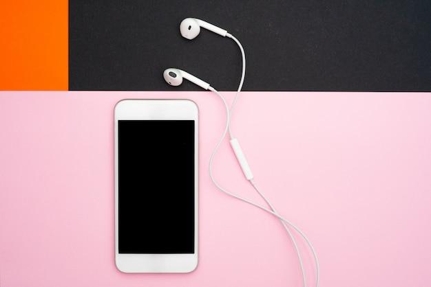 Musica, gadget, amante della musica. smartphone e cuffie bianchi sugli sfondi rosa arancioni, neri e molli con le cuffie.