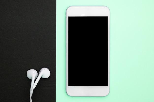 Musica, gadget, amante della musica. smartphone e cuffie bianchi. vista dall'alto vista piana, vista dall'alto.