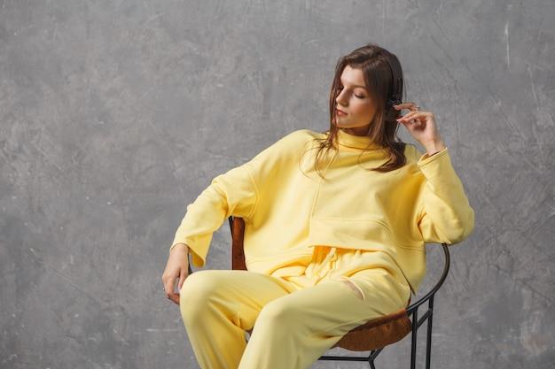 Musica per il buon umore. giovane donna in abiti sportivi gialli con cuffie wireless.