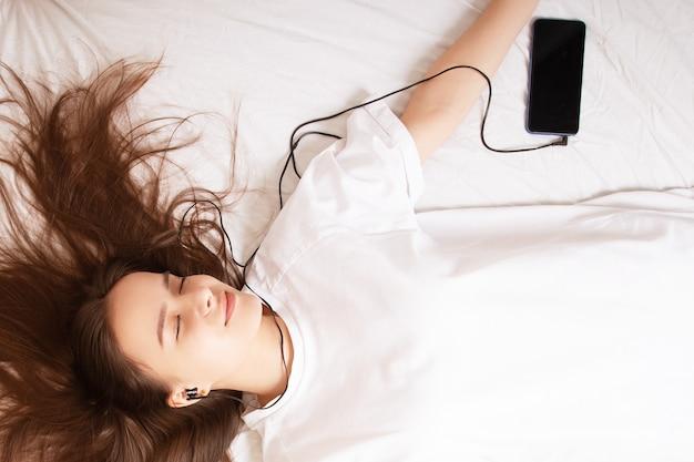 Stile di vita musicale. la ragazza in cuffia con un telefono con gli occhi chiusi si trova sul letto