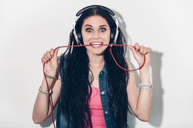 Amante della musica. bella giovane donna in cuffie che porta il filo in bocca e sembra eccitata mentre sta in piedi