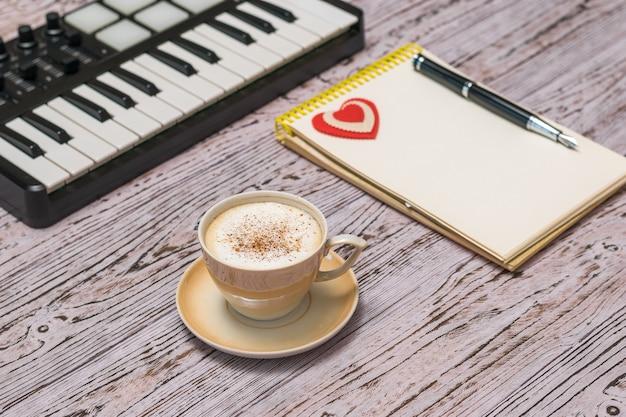 Un mixer musicale, una tazza di caffè e un taccuino su un tavolo di legno