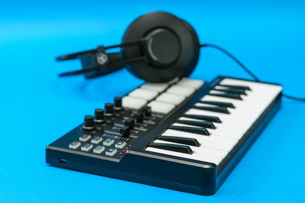 Mixer di musica e cuffie sulla superficie blu. attrezzatura per la registrazione di brani musicali.