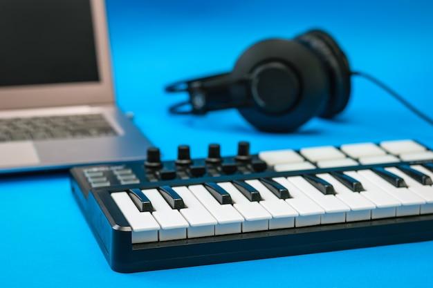Mixer musicale e cuffie e laptop su superficie blu. attrezzatura per la registrazione di brani musicali.