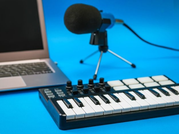 Mixer musicale, laptop e microfono con fili sulla superficie blu. attrezzatura per la registrazione di brani musicali.