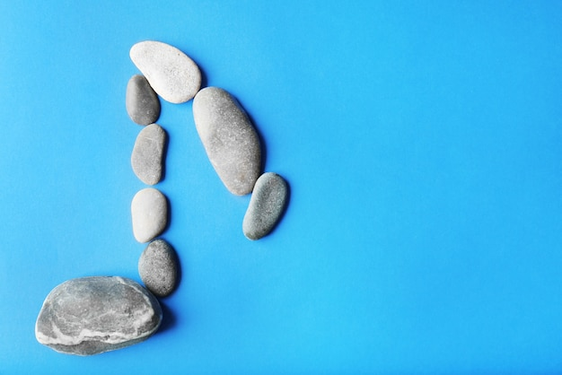 Segno di nota musicale fatto di pietre su sfondo blu