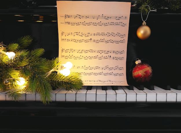 Note musicali sui tasti del pianoforte con decorazioni natalizie