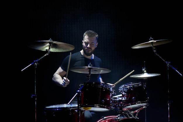 Musica, persone, strumenti musicali e concetto di intrattenimento - musicista maschio con bacchette che suonano batteria e piatti al concerto o in studio
