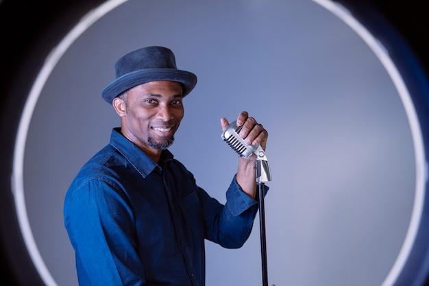 Music performer che canta una canzone con un microfono vintage argento. uomo afro etnico che esegue vecchia industria musicale. cantante maschio blues dell'afroamericano che tiene un mic professionale. stile ritmico e blues.