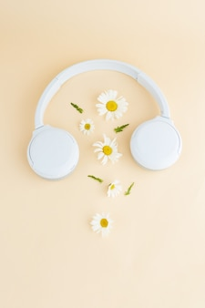 Musica o podcast di sottofondo con cuffie e fiori di camomilla margherita podcast estivo
