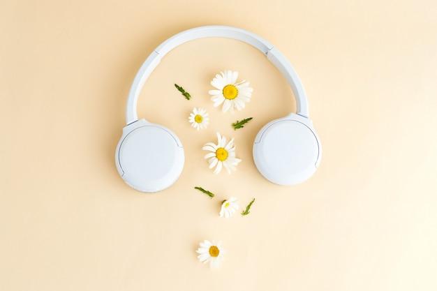 Sfondo di musica o podcast con cuffie e fiori di margherita (camomilla) su sfondo giallo. podcast estivo. vista dall'alto, posizione piatta