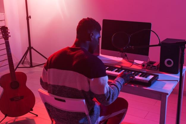 Concetto di produzione musicale - produttore di suoni maschile che lavora in uno studio di registrazione domestico.
