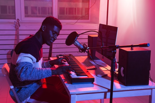 Concetto di produzione musicale. produttore del suono dell'uomo che lavora nello studio di registrazione domestico.