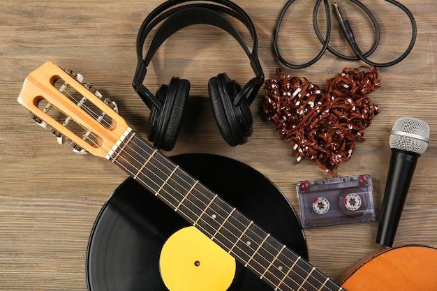 Scena di registrazione musicale con chitarra classica, disco in vinile, microfono, cassetta e cuffie su sfondo di legno