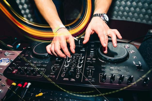 Telecomando musicale per informazioni e mixaggio di musica in discoteca con il primo piano delle mani del dj