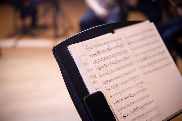 Primo piano dello spartito musicale sullo sfondo della sala da concerto