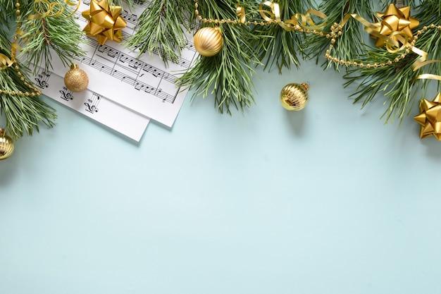 Fogli di musica per canti natalizi e canta palline dorate decorate su blu