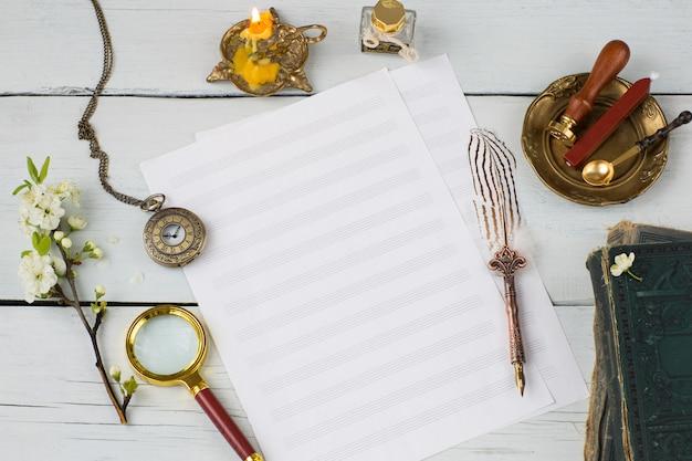 Fogli di musica, penna stilografica, orologio da tasca, libri antichi e ramo di ciliegio