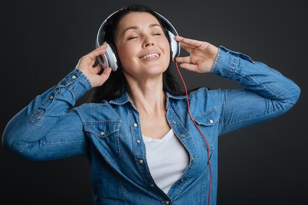 Estasi musicale. emotiva signora graziosa sognante che gode di una playlist perfetta pur avendo le cuffie e in piedi isolato su sfondo grigio