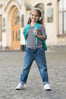 Esperienze musicali durante l'infanzia. il bambino felice ascolta la musica all'aperto. infanzia felice. scuola materna. educazione e cura della prima infanzia. insegnamento privato. giornata internazionale dei bambini.