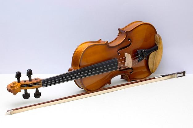 Violino di strumento musicale con fiocco su sfondo grigio