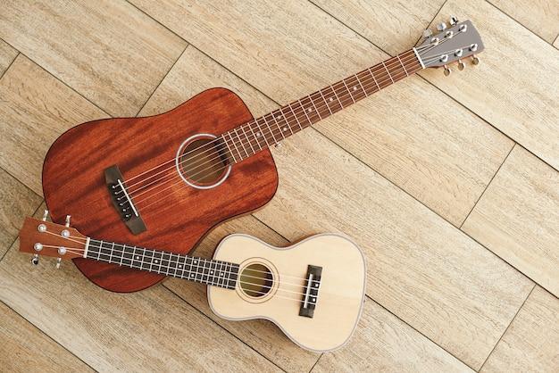 Sfondo di strumenti musicali vista dall'alto delle chitarre acustiche e ukulele che si trovano vicino a ciascuna