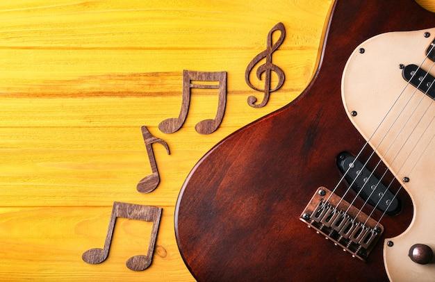 Note musicali e chitarra su legno giallo